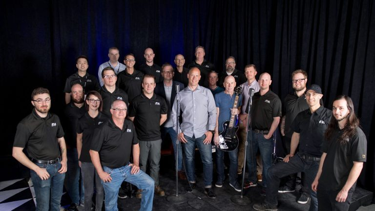 The FM Systems team, including President and CEO Marlin Jones (center) and Company Founder Terry Reeves (holding guitar)